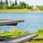 A picnic table near a lake on a warm summer day
